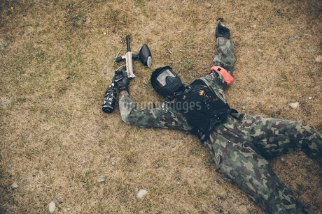 Man paintballing, collapsing in fieldの写真素材 [FYI02332293]