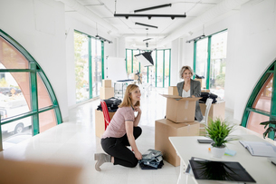 Female fashion designers unpacking jeans from cardboard boxes in new retail spaceの写真素材 [FYI02332318]