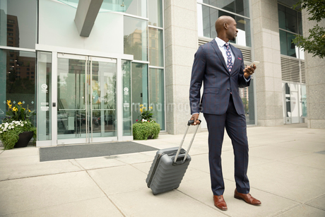 Businessman with suitcase using smart phone outside urban hotelの写真素材 [FYI02332359]