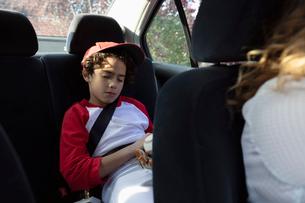 Tired Latinx boy in baseball uniform sleeping in back seat of carの写真素材 [FYI02332403]