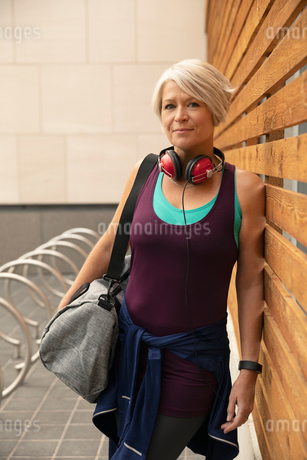 Portrait confident, athletic mature woman with gym bag and headphonesの写真素材 [FYI02332406]