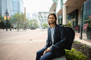Portrait man with backpack on city sidewalkの写真素材 [FYI02332503]