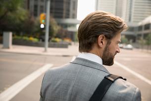 Rear view businessman crossing city streetの写真素材 [FYI02332527]