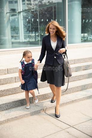 Businesswoman mother and schoolgirl daughter walking on urban sidewalkの写真素材 [FYI02332549]