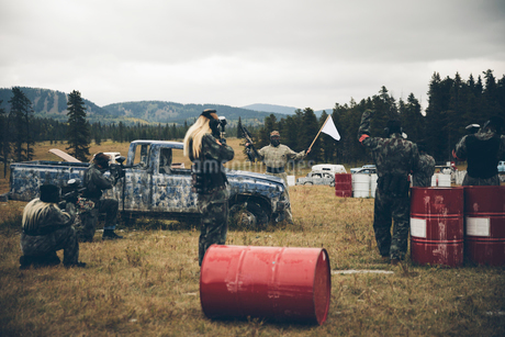 Man waving white flag at paintballing team in fieldの写真素材 [FYI02332582]