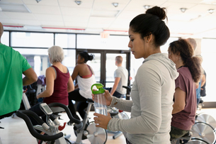 Woman with water bottle preparing for spin class in gymの写真素材 [FYI02332626]