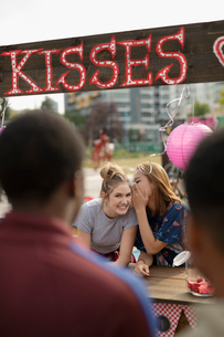 Teenage girls whispering, watching approaching boys at kissing boothの写真素材 [FYI02332636]