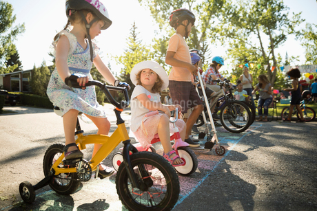 Kids on bicycles ready for race at starting line at summer neighborhood block partyの写真素材 [FYI02332640]