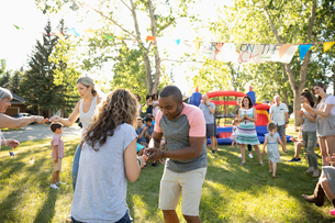 Neighbors enjoying egg and spoon race at summer neighborhood block party in parkの写真素材 [FYI02332790]