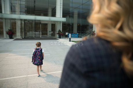 Businesswoman mother watching schoolgirl daughter watching on urban sidewalkの写真素材 [FYI02332859]