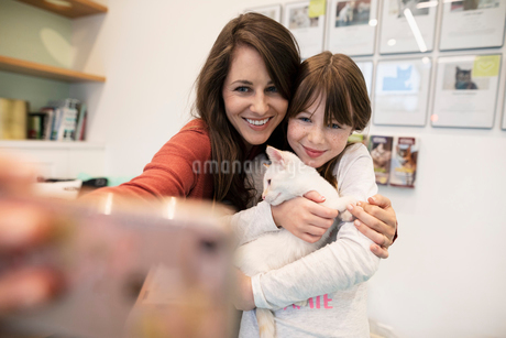 Mother and daughter holding kitten and taking selfie with smart phone in animal shelterの写真素材 [FYI02332917]
