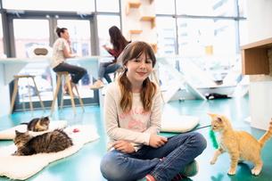 Portrait confident girl playing with kitten in cat cafeの写真素材 [FYI02332972]