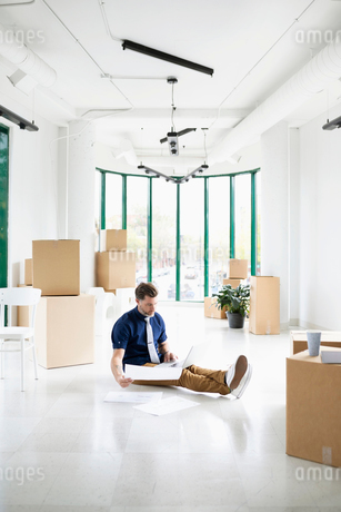 Businessman with laptop and blueprints in new, empty office space with cardboard boxesの写真素材 [FYI02333015]