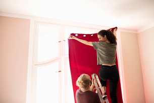 Couple on ladder hanging red curtainの写真素材 [FYI02333056]