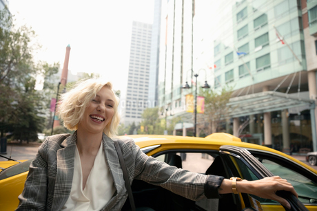 Laughing young businesswoman getting out of taxi on urban streetの写真素材 [FYI02333141]