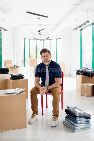 Portrait confident male business owner with stack of jeans in new retail spaceの写真素材 [FYI02333174]