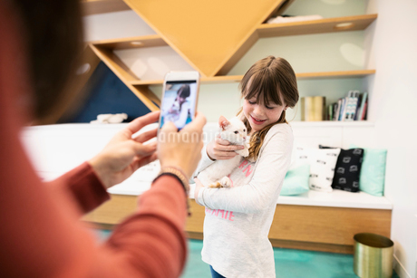 Mother with camera phone photographing daughter holding kittens in cat cafeの写真素材 [FYI02333184]