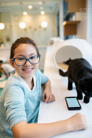 Portrait smiling, confident girl with cat in cat cafeの写真素材 [FYI02333215]