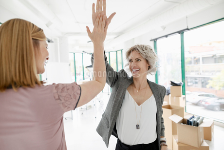 Excited female business owners high-fiving in new retail spaceの写真素材 [FYI02333230]