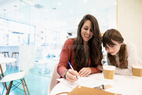 Smiling mother and daughter drinking coffee and filling out adoption application in cat cafeの写真素材 [FYI02333262]