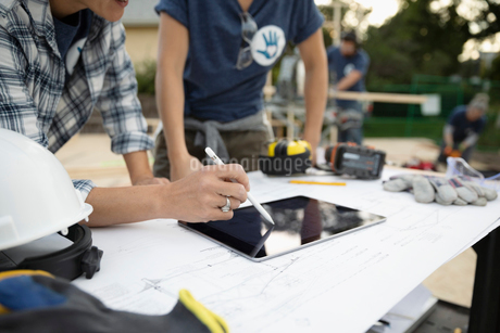 Male architect volunteers reviewing blueprints and using digital tablet, building houseの写真素材 [FYI02333303]