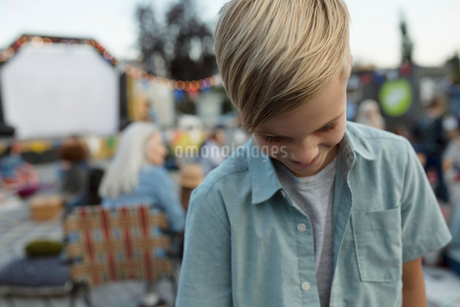 Smiling boy looking down at movie in the parkの写真素材 [FYI02333353]