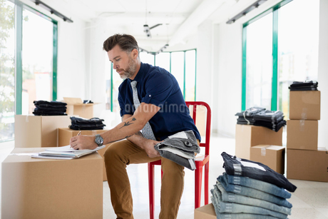 Male business owner checking inventory of jeans in new retail spaceの写真素材 [FYI02333451]