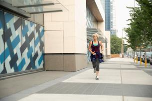 Athletic mature woman running on urban sidewalkの写真素材 [FYI02333491]
