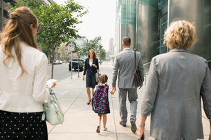 Businessman father and schoolgirl daughter holding hands and walking on urban sidewalkの写真素材 [FYI02333496]