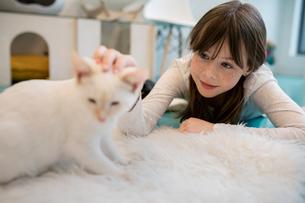 Girl petting kitten in cat cafeの写真素材 [FYI02333554]