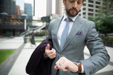 Businessman checking the time on wristwatch on urban sidewalkの写真素材 [FYI02333585]