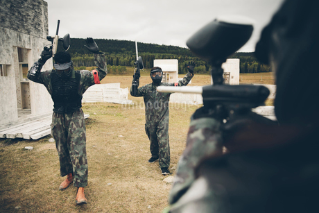 Paintballing team surrendering in fieldの写真素材 [FYI02333617]
