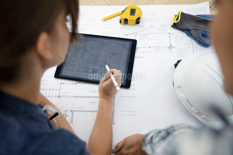 Female architect volunteers reviewing blueprints and using digital tablet, building houseの写真素材 [FYI02333649]