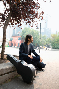 Male musician with guitar case on urban sidewalkの写真素材 [FYI02333671]