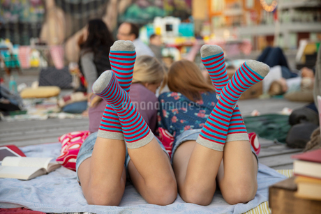 Teenage girls with  matching socks relaxing in parkの写真素材 [FYI02333681]
