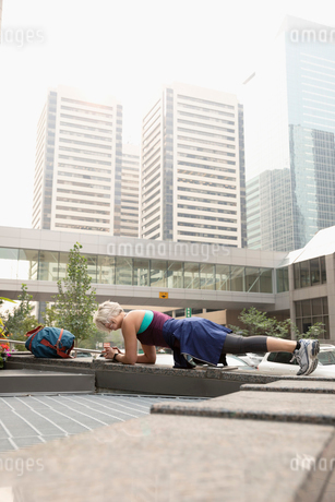Athletic mature female runner exercising, in plank position in cityの写真素材 [FYI02333761]