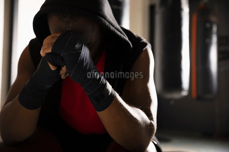 Tired male boxer with head in hands, resting in gymの写真素材 [FYI02333905]