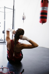 Female boxer doing sit-ups in gymの写真素材 [FYI02333907]
