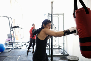 Tough female boxer training at punching bag in gymの写真素材 [FYI02333915]
