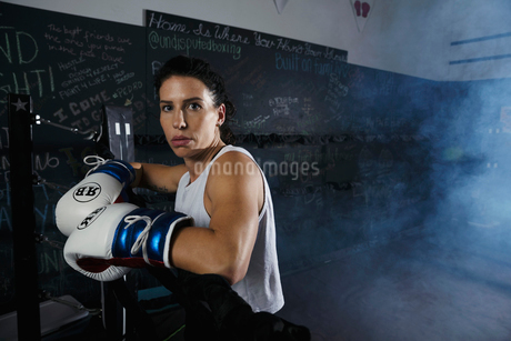 Portrait tough female boxer standing in boxing ringの写真素材 [FYI02333920]