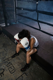 Tired female boxer resting in gymの写真素材 [FYI02333923]