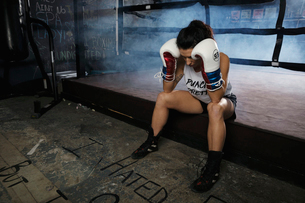 Tired female boxer resting in gymの写真素材 [FYI02333944]