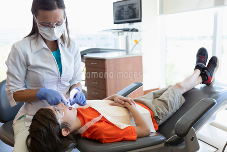 Dental hygienist flossing teeth of boy in dentist officeの写真素材 [FYI02333950]