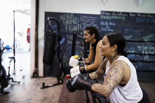 Female boxer with tattoos resting in gymの写真素材 [FYI02333953]