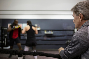 Trainer watching boxers training in boxing ring in gymの写真素材 [FYI02333965]