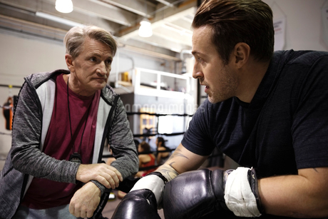 Trainer and male boxer talking in gymの写真素材 [FYI02333975]