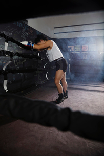 Tired female boxer resting in boxing ringの写真素材 [FYI02333978]