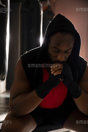 Male boxer in hoody resting in gymの写真素材 [FYI02334003]
