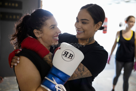 Happy female boxers hugging in gymの写真素材 [FYI02334005]