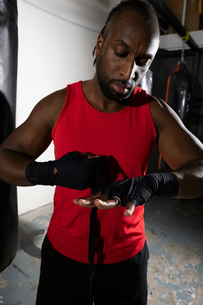 Male boxer wrapping wrists with tape in gymの写真素材 [FYI02334022]
